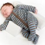 Baby sover sikkert på siden med en sidekilepude